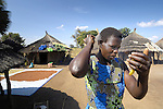 A woman displaced by internal conflict in northern Uganda has returned to her village of origin, where she has built a new hut and checks her hair in a mirror. The two-decade long conflict began winding down with peace talks in 2006, and in 2007 a few families left camps for the internally displaced and returned to their original villages.