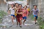 Children run through the streets in Pulilan, a village in Bulacan, Philippines, where the Kapatiran-Kaunlaran Foundation (KKFI) sponsors a preschool. <br /> <br /> KKFI is supported by United Methodist Women.