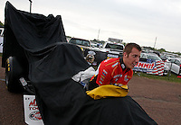 Apr. 27, 2013; Baytown, TX, USA: A crew member for NHRA top fuel dragster driver Doug Kalitta steers the car as they head back to the pits during a rain delay to qualifying for the Spring Nationals at Royal Purple Raceway. Mandatory Credit: Mark J. Rebilas-