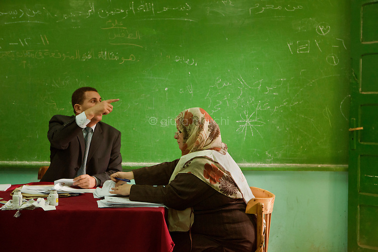 Egypt / Zagazig / 15.12.2012 / The judge and a woman of the organisation manage Egyptians casting their ballots. People descended on polling stations across Egypt to vote on the highly controversial draft constitution, which has been a source of intense political protest in recent weeks. <br /> <br /> © Giulia Marchi
