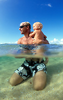 Hawaii, Kauai, Father & 13 m.o. baby girl in ocean, split level view.