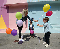 Roman Smolinski, 3, (right) and his twin sister, Charleston Smolinski are given balloons by their mother, Ally Smolinski of Rogers, Thursday, May 21, 2020, while taking family photographs in front of the Maude Wall at Maude Boutique in Fayetteville. The clothing store invites patrons to use their multicolored back wall for photographs. Visit nwaonline.com/200522Daily/ for today's photo gallery.<br /> (NWA Democrat-Gazette/Andy Shupe)