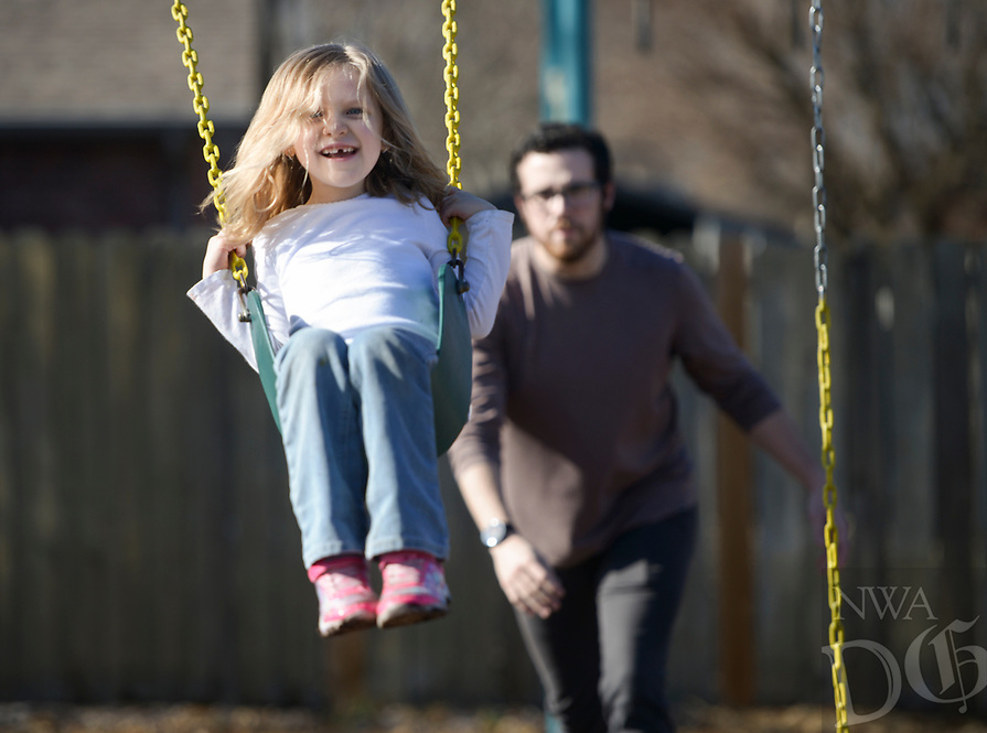 NWA Democrat-Gazette/CHARLIE KAIJO Teen Director Bryan Collom pushes Sarah Lundy, 6, of Bentonville on a swing (from right), Monday, January 7, 2019 at the Boys and Girls Club in Bentonville. <br />