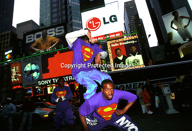 A dance group performing on a sidewalk at night in Times Square on April 25, 1997 in New York City, New York, USA. Times Square has been totally renovated and upgraded and most sex shops and thieves have dissapeared.  Theme restaurants and financial companies has moved in..(Photo: Per-Anders Pettersson/ Liaison Agency)