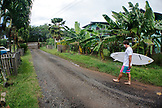 USA, Oahu, Hawaii, portrait of MMA Mixed Martial Arts Ultimate fighter Lowen Tynanes walks down Sunny Garcia's driveway on his way to surf at Pipeline on the North Shore of Oahu