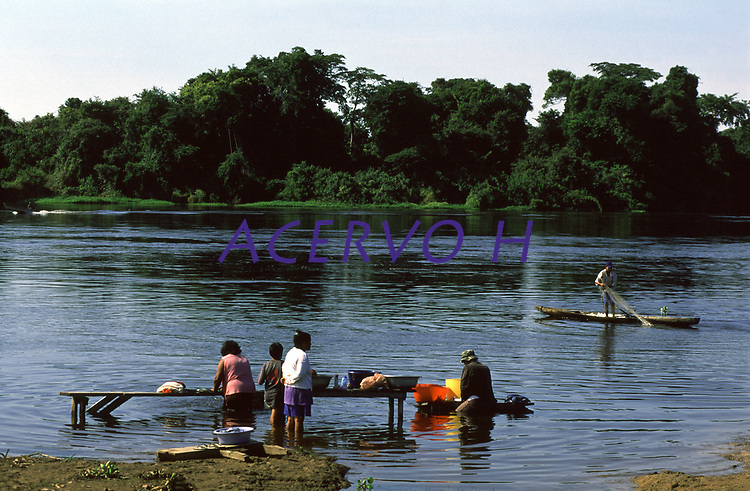 mulheres lavando roupas e homem pescando com tarrafa no rio Guaporé em Rondônia, na divisa entre Brasil e Bolívia.