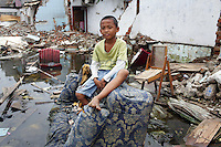 A boy sits on a discarded sofa in a flooded district in the northern port area of Jakarta. Almost 40% of Jakarta lies below sea-level leading to flooding in many areas, even during the dry season.