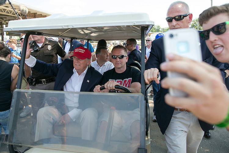 UNITED STATES - August 15: Republican presidential candidate Donald Trump greets fairgoers as he arrives at the Iowa State Fair on a golf cart as a man attempts to take a selfie with him in Des Moines, Iowa, on Saturday, August 15, 2015. (Photo By Al Drago/CQ Roll Call)