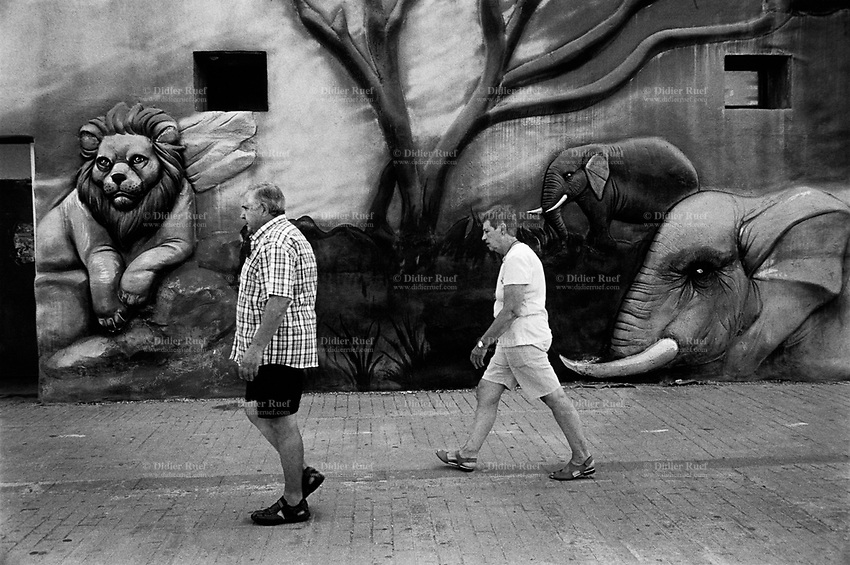 Spain. Valencian Community. Oropesa del Mar. The project of Marina d'Or (Ciudad de Vacaciones)) began in the mid-1990s. At first it looked like a traditional tourist urbanization, but in less than 15 years it became a major tourist project. An elderly couple walks on a sidewalk and passes by a painted wall with a lion and two elephants.<br /> The lion is a species in the family Felidae; it is a muscular, deep-chested cat with a short, rounded head, a reduced neck and round ears, and a hairy tuft. The elephants are the large mammals forming the family Elephantidae in the order Proboscidea. Three species are currently recognised: the African bush elephant (Loxodonta africana), the African forest elephant (L. cyclotis), and the Asian elephant (Elephas maximus). <br /> Oropesa del Mar (Valencian: Orpesa) is a municipality in the comarca of Plana Alta in the Valencian Community. An autonomous community is a first-level political and administrative division, created in accordance with the Spanish constitution of 1978, with the aim of guaranteeing limited autonomy of the nationalities and regions that make up Spain. 13.09.2018 © 2018 Didier Ruef