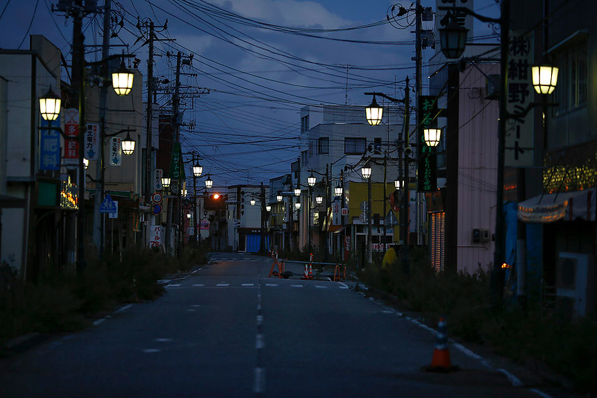 Street lamps light the street in the evacuated town of Namie in Fukushima prefecture September 23, 2013. Namie's more than 20,000 residents can visit their homes once a month with special permissions but are not allowed to stay overnight inside the exclusion zone. A total of 160,000 people had been forced to leave their homes around Daiichi plant after the government ordered the evacuation following the nuclear disaster in March 2011.  REUTERS/Damir Sagolj (JAPAN)