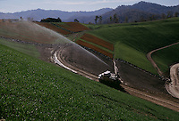 A truck sprays chemicals and seeds a hillside to regrow plants on a barren hillside. The hills was leveled after coal removed in a reclamation project. Small mountaintop removal site employes a small number of workers that are cleaning up what a large company left as rubble.
