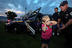 NHP Trooper Sean Giurlani reaches to comfort Kira Breeden, 3, as all the sirens sound marking the end of the 11th annual National Night Out hosted by the Carson City Sheriff's Office in Carson City, Nev., on Tuesday, Aug. 6, 2013. <br /> Photo by Cathleen Allison