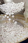 Drug production. Drug tablets spill into a container on part of a production line. Royalty Free