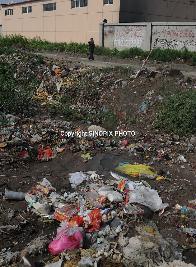 "Factories at Xiditou have piles of rubbish and chemical waste outside. Xiditou is known as one of China's worse ""cancer villages"" where a reported ten percent have died from cancer."