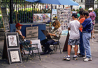 New Orleans, Louisiana.  French Quarter.  Caricaturist Drawing a Client's Portrait.