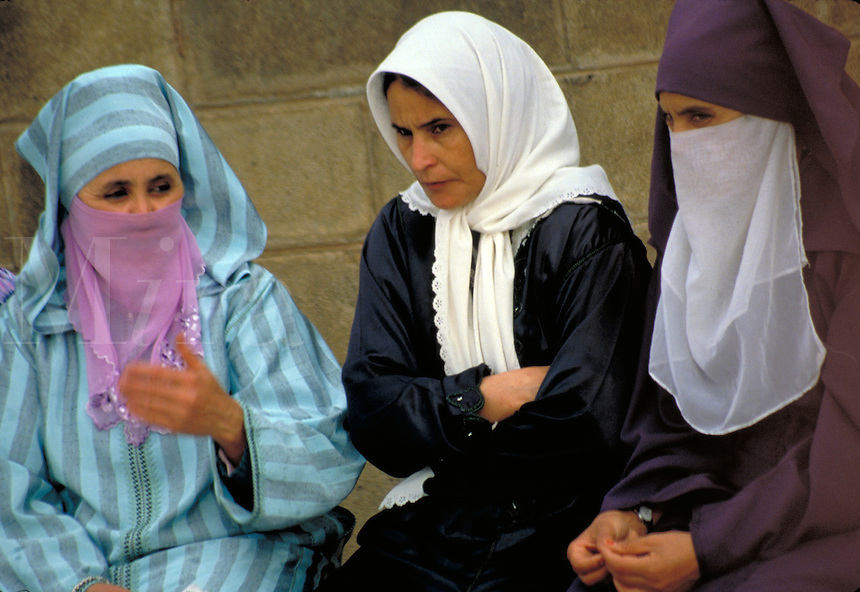 Three veiled women display different levels of Islamic modesty in public in Morocco. Some cover their face while others cover only their hair. Tangiers, Morocco.