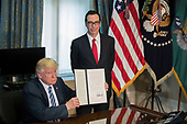 US President Donald J. Trump (L), with Secretary of Treasury Steven Mnuchin (R), displays a signed financial services Executive Order during a ceremony in the US Treasury Department building in Washington, DC, USA, 21 April 2017. President Trump is making his first visit to the Treasury Department for a memorandum signing ceremony with Secretary Mnuchin.<br /> Credit: Shawn Thew / Pool via CNP