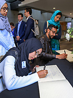Victoria University student Iffah Abdul Kahim signs the book of remembrance. Members of the NZ Parliament pay tribute to Christchurch terror attack victims at Parliament in Wellington, New Zealand on Monday, 18 March 2019. Photo: Dave Lintott / lintottphoto.co.nz