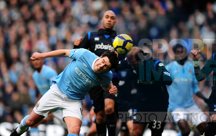 Gareth Barry of Manchester City tries to head the ball towards the goal under pressure from Aggelos Basinas of Portsmouth