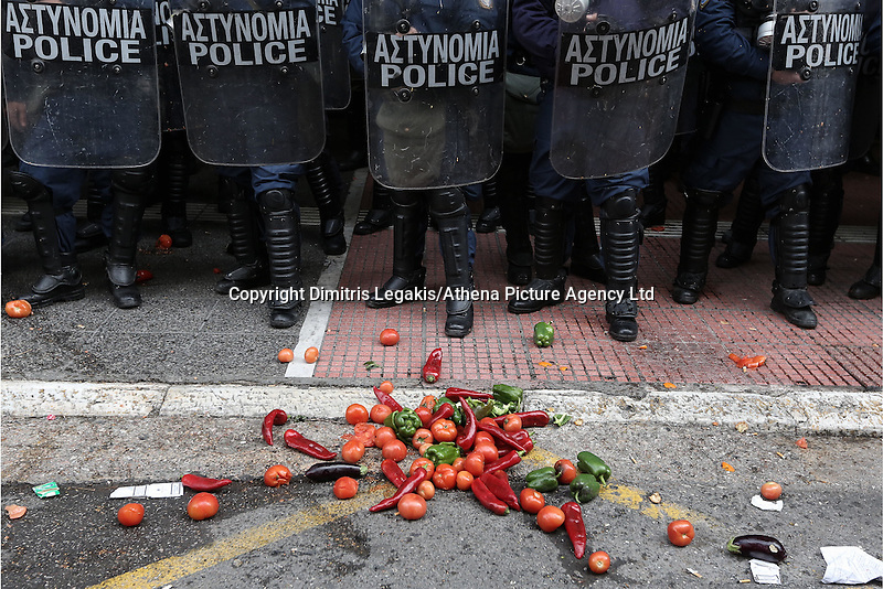 Pictured: Fresh produce is placed in front of riot police by the farmers Friday 12 February 2016<br />Re: Violent clashes between farmers and riot police outside the Ministry of Agricultural Development in Athens, Greece. The farmers travelled from Crete to protest against pension and welfrae reforms proposed by the Greek government,