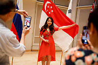 Nicolette Chin of Singapore poses with her country's flag after the opening ceremony of the 11th USA International Harp Competition at Indiana University in Bloomington, Indiana on Wednesday, July 3, 2019. (Photo by James Brosher)