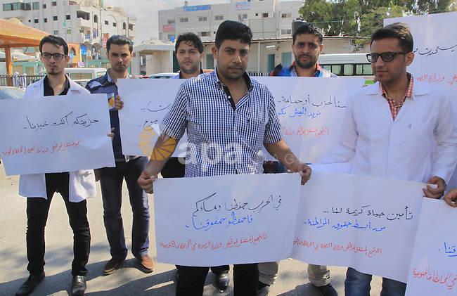 Palestinian Doctors of the formerly Hamas-run government in the Gaza Strip hold banners during a protest to demanding their salaries, at Shifa hospital in Gaza city, on October 15, 2014. Photo by Mohammed Asad