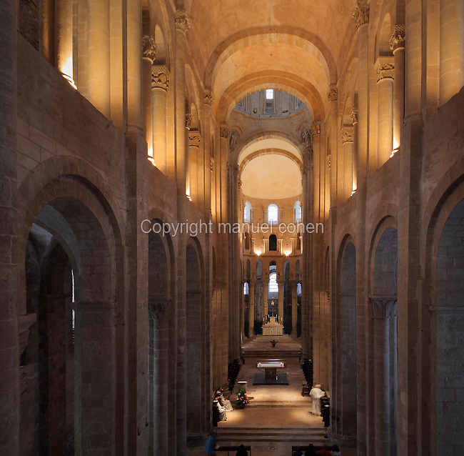 Nave and choir, seen from the organ gallery, in the Abbatiale Sainte-Foy de Conques or Abbey-church of Saint-Foy, Conques, Aveyron, Midi-Pyrenees, France, a Romanesque abbey church begun 1050 under abbot Odolric to house the remains of St Foy, a 4th century female martyr. The 20.7m high nave is barrel-vaulted and supported by columns and arches along each side. The church is on the pilgrimage route to Santiago da Compostela, and is listed as a historic monument and a UNESCO World Heritage Site. Picture by Manuel Cohen