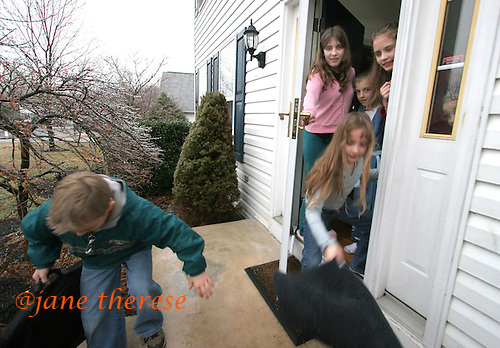 The Salem children, 3 sets of twins from Nevel, Russia who now live in Telford, Pa., are all very close to each other. Here Sophia 8 (center foreground), lays a mat down for Jake as he makes his way down the icy sidewalk on his way to guitar lessons. Julianne 13 (top left), Sam Jakes twin (center), and Selene, Julianne's twin along with Joseph peeking out the window (right), watch as Jake leaves for the afternoon on a cold Thursday March 2, 2006. Sophia and twin Joseph were adopted at 11 months of age by Hythem and his wife Lisa. The other twins, Selene and Julianne 13 along with Sam and Jake 12, were adopted just 20 months ago. All children are thriving in school, socially and physically. photo by jane therese