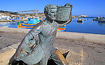 Fisherman statue sculpture in harbour at fishing village of Marsaxlokk, Malta
