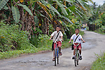 "Elabome Hia and Kristiano Hia, both 11 years old, ride their bikes home from school in Tugala, a village on the Indonesian island of Nias. The village was struck by both a 2004 tsunami and a 2005 earthquake, leaving houses destroyed and lives disrupted. The ACT Alliance helped villagers here to construct new homes and latrines, build a potable water system, open a clinic and schools and get their lives going once again. For the residents of Tugala, the post-disaster mantra of ""build back better"" became a reality with help from the ACT Alliance."