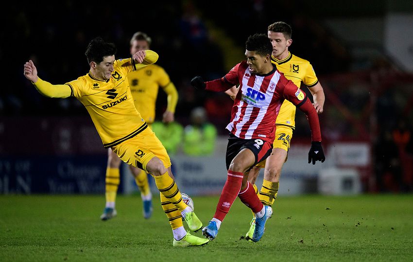 Lincoln City's Tyreece John-Jules vies for possession with Milton Keynes Dons' George Williams<br /> <br /> Photographer Chris Vaughan/CameraSport<br /> <br /> The EFL Sky Bet League One - Lincoln City v Milton Keynes Dons - Tuesday 11th February 2020 - LNER Stadium - Lincoln<br /> <br /> World Copyright © 2020 CameraSport. All rights reserved. 43 Linden Ave. Countesthorpe. Leicester. England. LE8 5PG - Tel: +44 (0) 116 277 4147 - admin@camerasport.com - www.camerasport.com