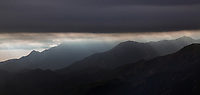 aerial photograph of light rays breaking through a layer of fog at coastal mountains in Ventura County, California