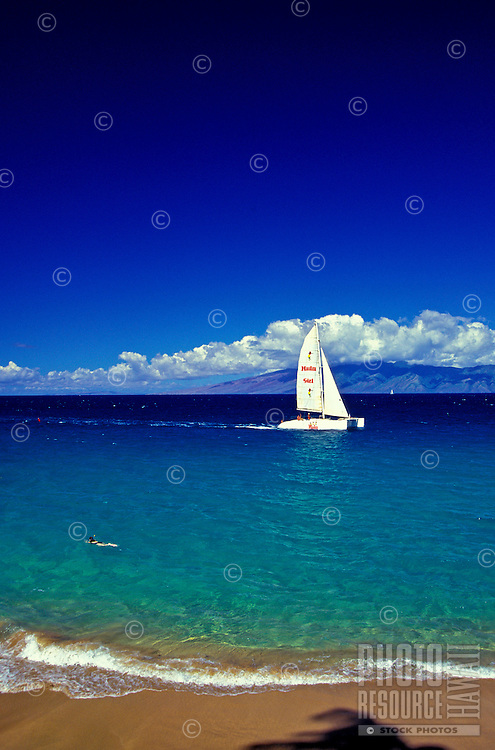 Sailing and snorkeling off Prendal beach, locally known as Old Airport Beach. The island of Molokai and a canopy of clouds in the background.
