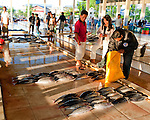 Customers count out payment as a vendor packs fresh fish into their bag, at the early morning fish market in Bitung (the largest seaport in the Lembeh Strait, North Sulawesi, Indonesia).