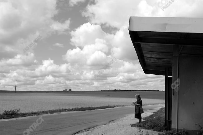 A woman waited at a bus stop near the town of Stanovoye in the Lipetsk region as crops ripened in the fields nearby. Russia, July 30, 2008.