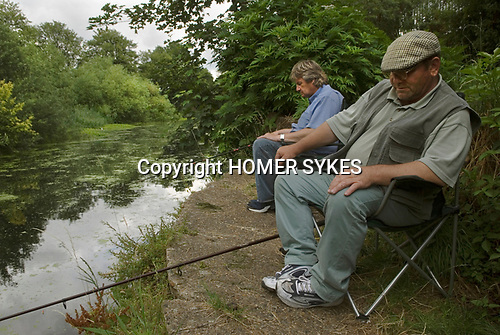 Fishermen fishing the old River Lea. East London the site of the 2012 Olympic Games village and arena, Hackney Marsh, Stratford, England 2006.