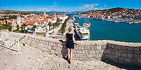 Panoramic photo of a tourist admiring the view from Kamerlengo Fortress (Gradina Kamerlengo) over Trogir water front, Dalmatian Coast, Croatia, Europe. This panoramic photo shows a tourist admiring the view of Obala Bana Berislavica, the main road along the water front in Trogir. It shows Kamerlengo Fortress (Gradina Kamerlengo) in the foreground and from right to left, the three main Cathedral bell towers that are visible are; Church and Monastery of St Dominic, Cathedral of St Lawrence and St Michael Monastery Church Bellfry. Trogir is a beautiful old town on the Dalmatian Coast of Croatia and is on the UNESCO World Heritage List thanks to it's stunning Romanesque Cathedral's and architecture. Inside the walls of the old town Trogir, the cobbled streets are complemented by beautiful buildings and towering spires. After visiting the many sites, there is always the option of a walk along Obala Bana Berislavica, the main street along the waterfront in Trogir that runs alongside the bright blue Adriatic Sea of the Dalmation Coast of Croatia.