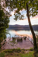 Morning sunrise on a deck bordering a volcano lake at Ndali lodge, Uganda, Africa