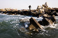 A fisherman walks across sea wall defences in Jingtang harbour, Hebei province. This stretch of coastline has been highlighted as one of the most vulnerable in China and will be one of the first to feel the impacts of rising sea levels and increased storm surges. China, 2019.