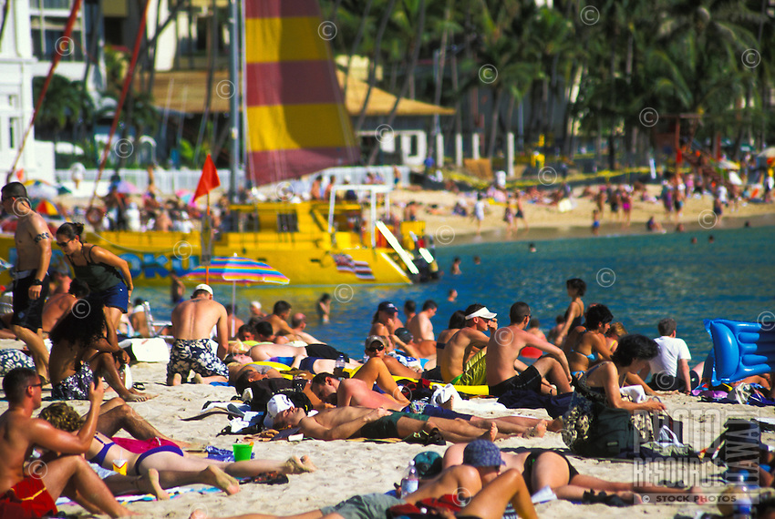 Waikiki beach with crowds on a hot day, with catamaran, island of Oahu