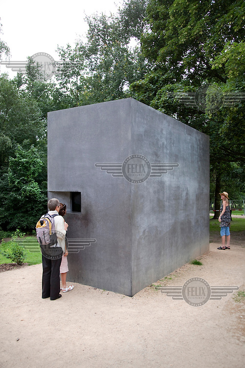 Berlin memorial to gay victims of the Nazis in the Tiergarten Park consists of a concrete block with a small window. Viewed through the window is a continually repeating video showing a gay couple kissing..