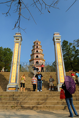 Asia, Vietnam, Hue. Tourists at the Thap Phuoc Duyen (Source of Happiness Tower) at Thien Mu (Heavenly Lady Pagoda). Designated a UNESCO World Heritage Site in 1993, Hue is honoured for its complex of historic monuments. Overlooking the river Huong (Perfume River) and set amidst verdant greenery, the Thien Mu Pagoda is the oldest pagoda in Hue. Built in 1601 the 21meter high seven-story octogonal tower Thap Phuoc Duyen is now the official symbol of the city Hue.