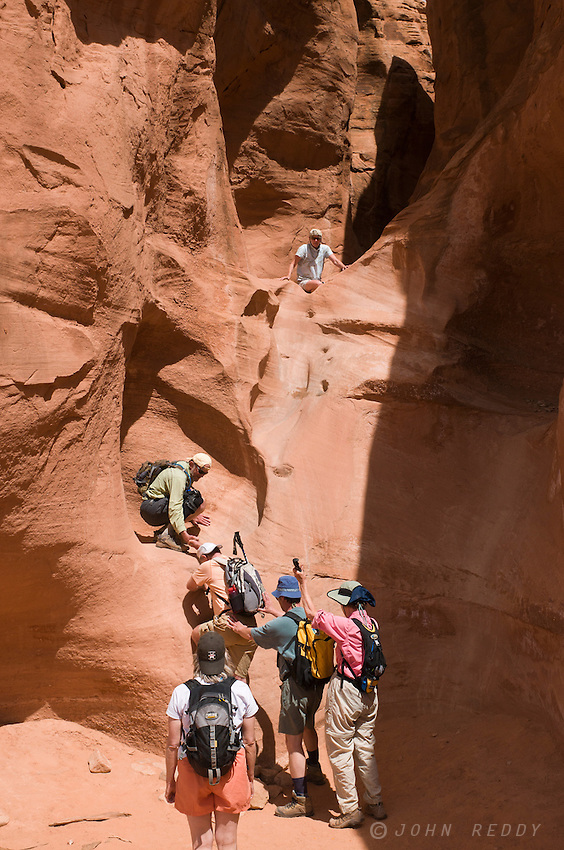 Hikers climbing into the entrance of Peekaboo Canyon
