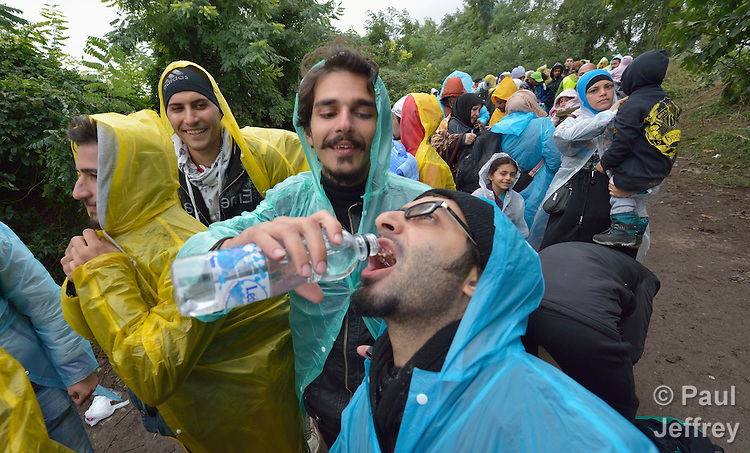 A man helps another drink water as refugees and migrants approach the border into Croatia near the Serbian village of Berkasovo. Hundreds of thousands of refugees and migrants--from Syria, Iraq and other countries--have flowed through Serbia in 2015, on their way to western Europe.