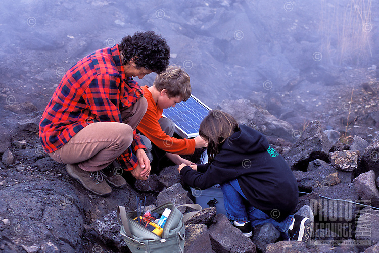 Women scientist and kids at Hawaii Volcanoes National Park working with gas samples from Kilauea volcano lava flows