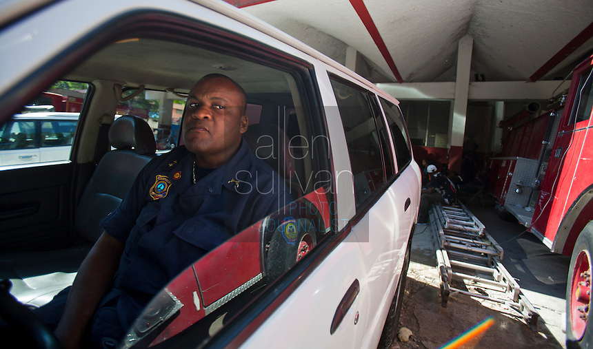 Chief Donald Grégory William uses his air-conditioned car as an office at the Port-au-Prince, Haiti fire station. The building was heavily damaged in the January 12 earthquake and has been deemed uninhabitable and marked for demolition, though no one can say when that may be. William says he spends as little time as necessary inside the structure, as he doesn't trust it. There are no plans yet for relocation. A few dozen under-equipped firefighters are tasked with providing fire service to a damaged city of over two million people.