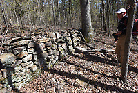 NWA Democrat-Gazette/FLIP PUTTHOFF <br /> Tim Garton looks at a rock fence April 12 2019 that is seen on the hike to the waterfall area.