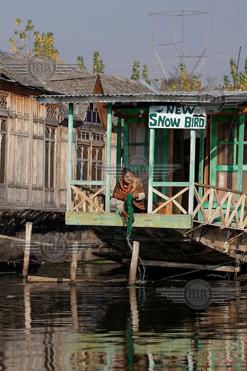 A woman rinses clothes on the porch of a house boat on Dal Lake. Srinagar, Kashmir, India. © Fredrik Naumann/Felix Features