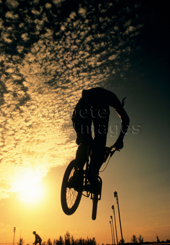 Silhouette of track cyclist in silhouette as he jumps