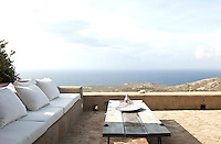 The terrace affords views over the rocky landscape of Mykonos to the Mediterranean